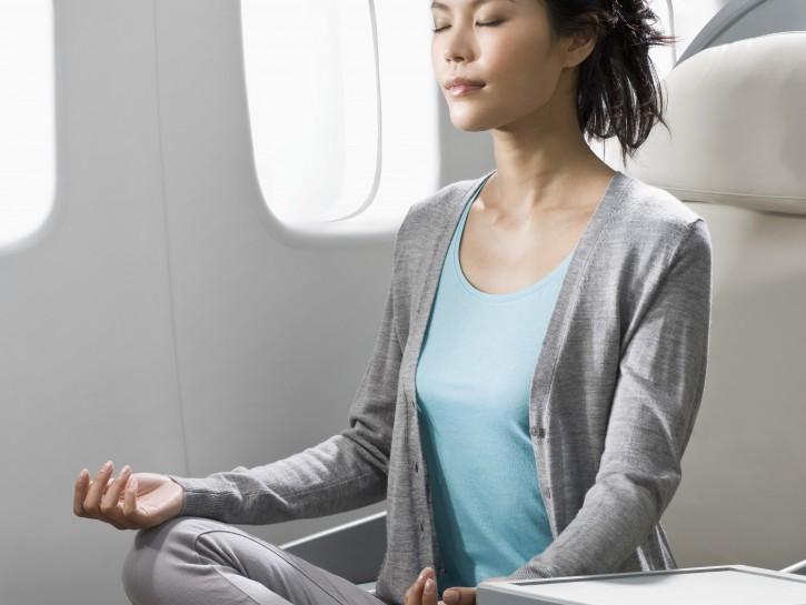 Woman meditating on airplane