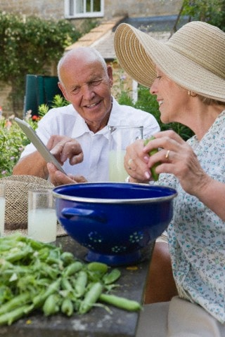 Senior Couple Relaxing On Patio Outside Cottage