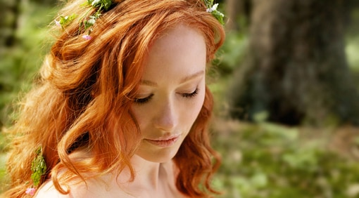 Beautiful woman with long red hair in forest