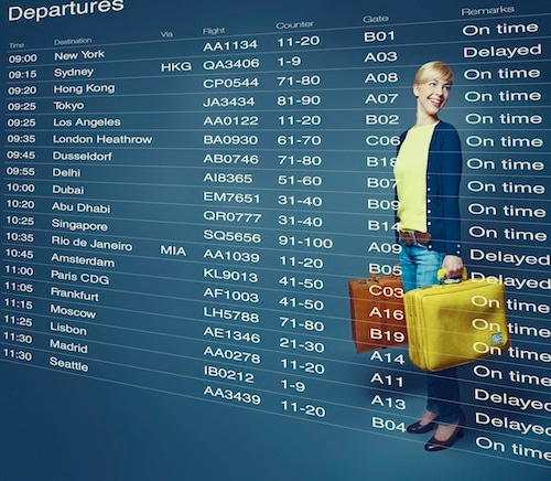 Composite image of young woman standing in front of departures board
