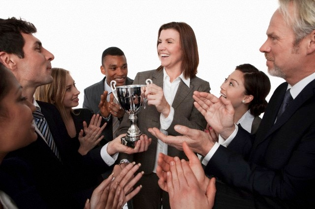 Businesswoman receiving trophy, colleagues clapping