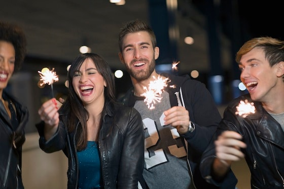 Friends celebrating New Year's Eve with sparklers outdoors