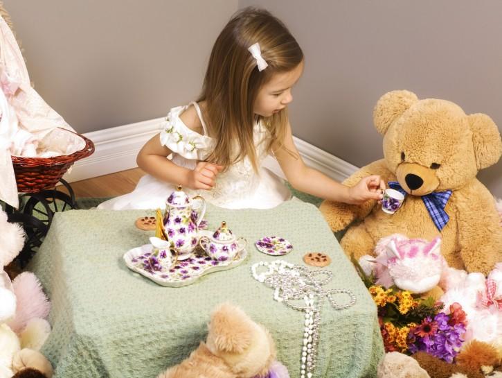 Girl having a tea party with teddy bears