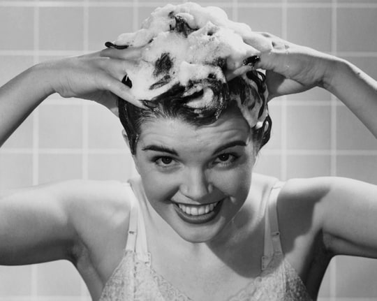 Young woman shampooing her hair
