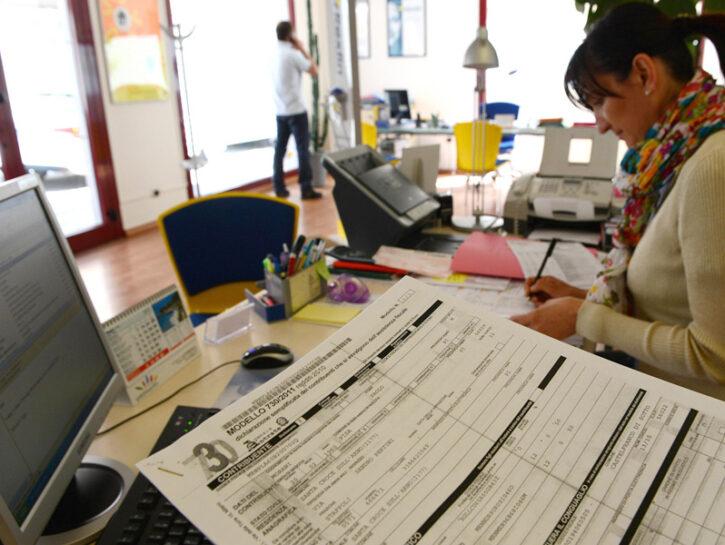 Una ragioniera lavora ad un modello 730 nell'ufficio di un commercialista