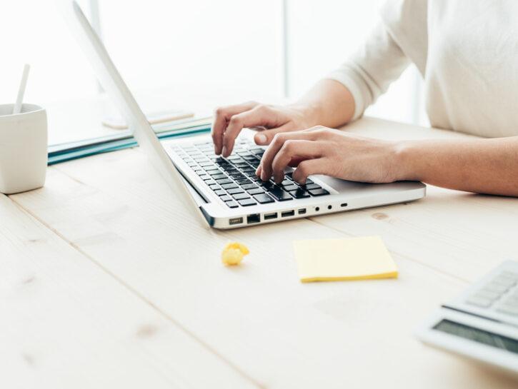 Donna scrive al computer in casa
