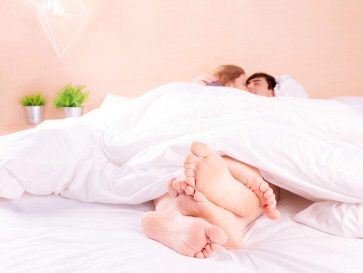 Coppia a letto piedi intrecciati