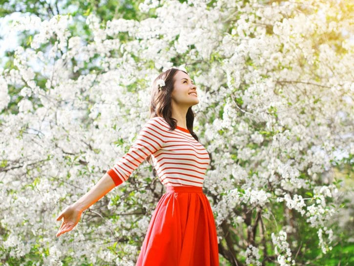 Ragazza rosso in mezzo alberi in fiore