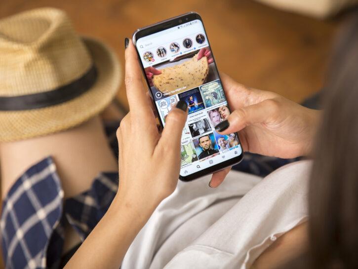 Instagram-Ragazza-con-cellulare-in-mano-cappello