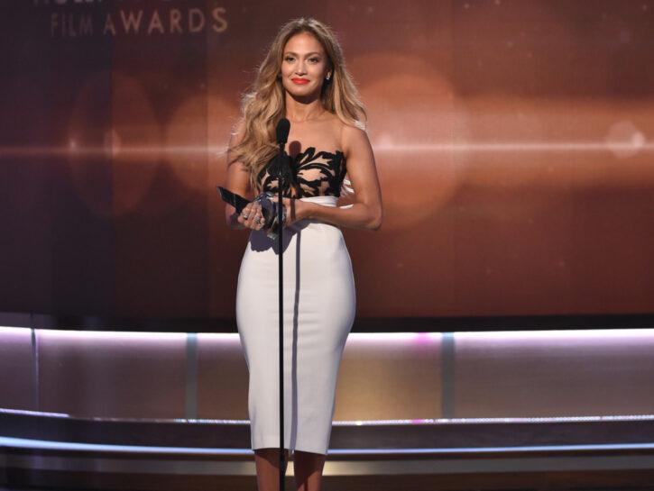 Jennifer Lopez in tubino bianco aderente che esalta il suo sinuoso fisico a pera
