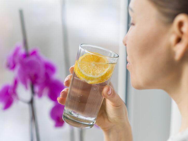 Donna bicchiere acqua limone con orchidea