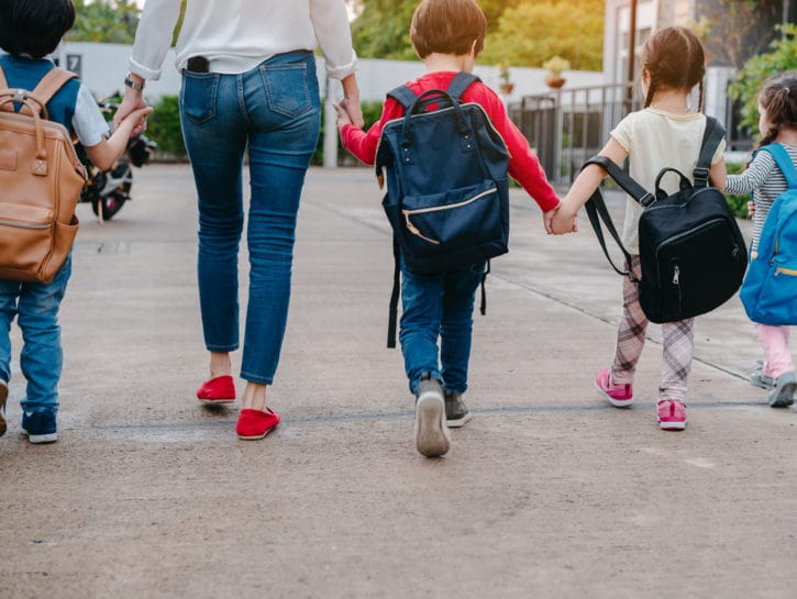Mamma con bambini a scuola zaini