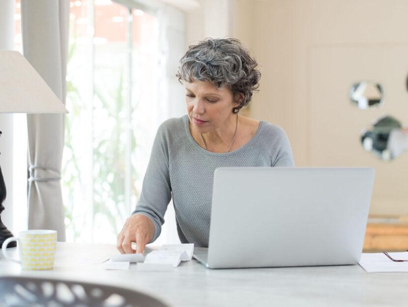 Donna mezza eta computer cucina