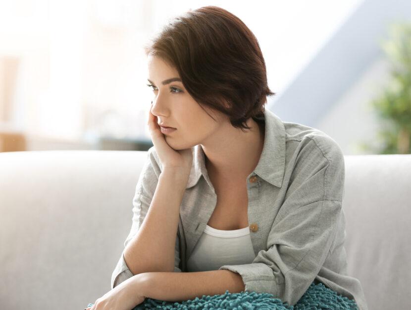 Donna pensierosa su divano