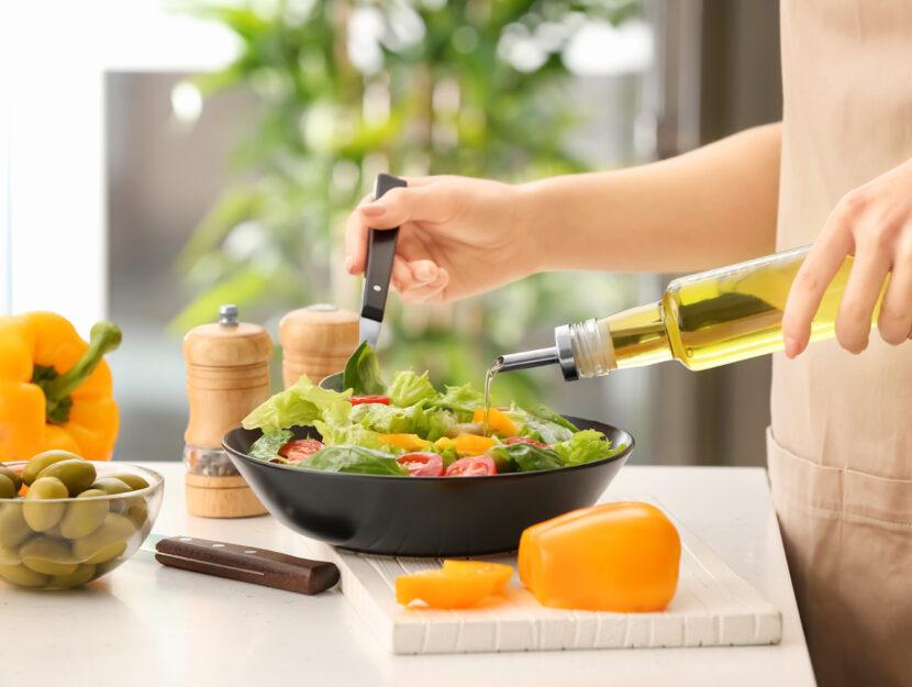 Donna cucina verdura olio