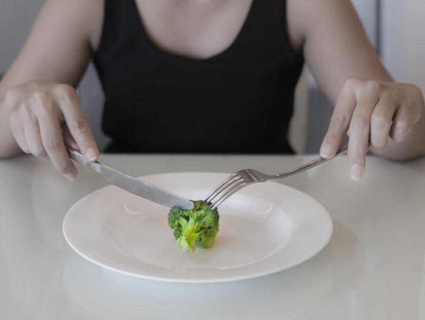 Donna mangia piatto di broccoli