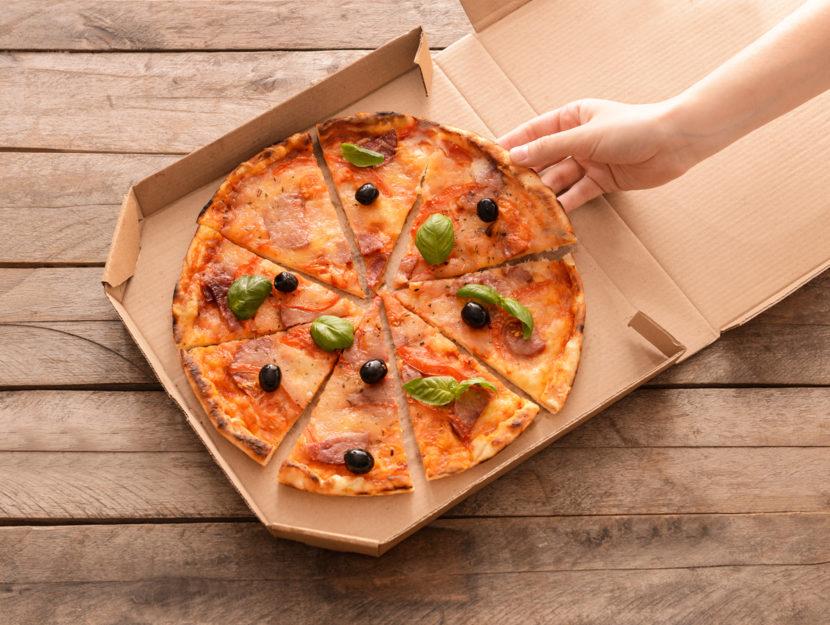 Pizza nel cartone con mano di donna