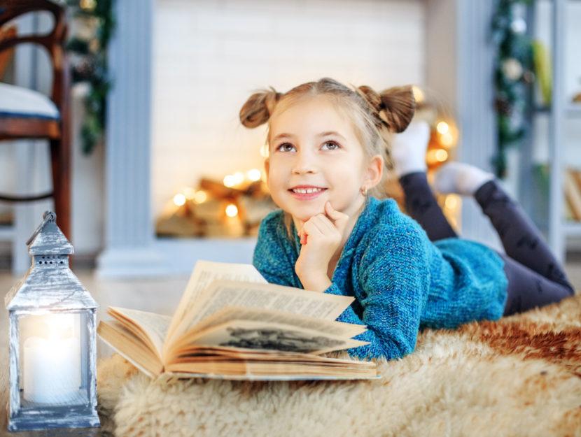 Bambina legge libro inverno camera