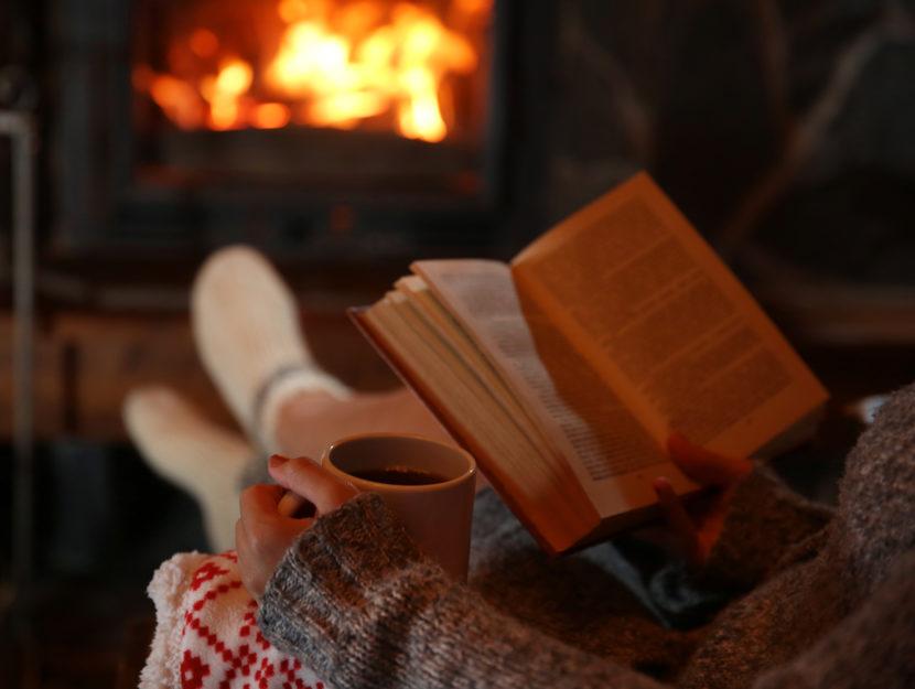 Ragazza legge libro inverno caminetto