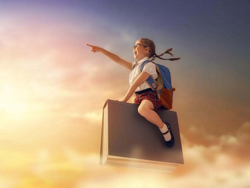 Bambina in volo su libro