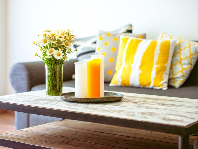 tavolino di legno con candele e vaso di margherite