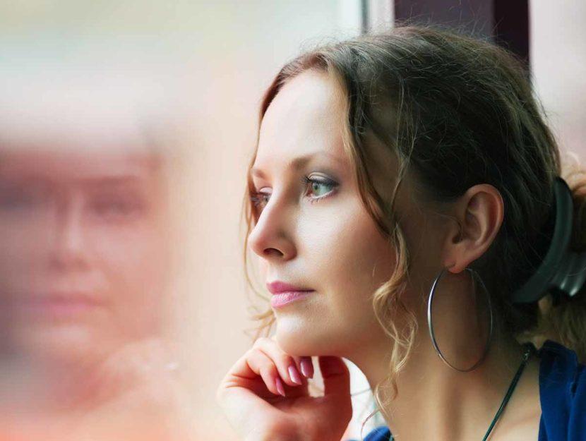 donna triste che guarda fuori dal vetro