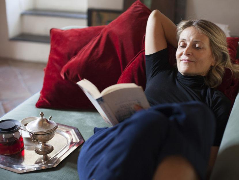 Donna legge libro sul divano