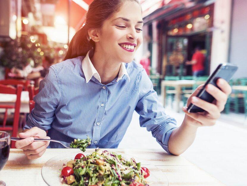 Ragazza che mangia e usa lo smartphone