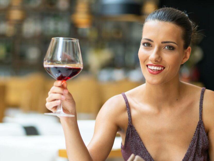 Donna elegante con calice di vino rosso