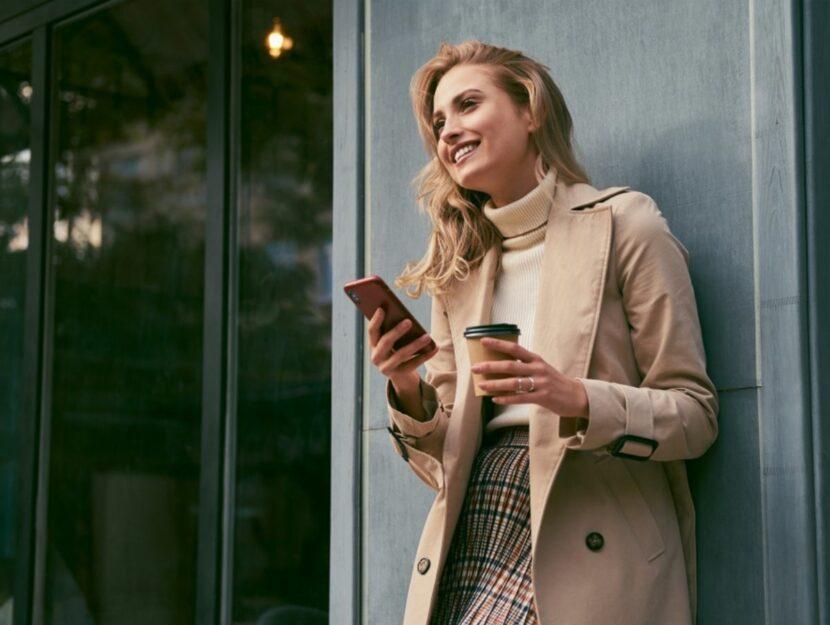 Donna beve caffè e sta al cellulare