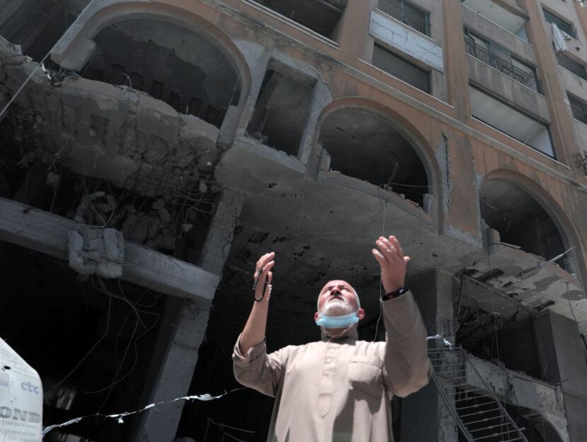 Un uomo palestinese di fronte alla Al-Jawhara Tower di Gaza City, colpita dagli attacchi aerei israe
