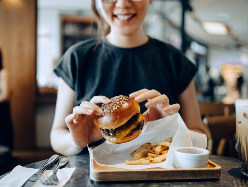 donna che mangia hamburger, cattive abitudini, fast food