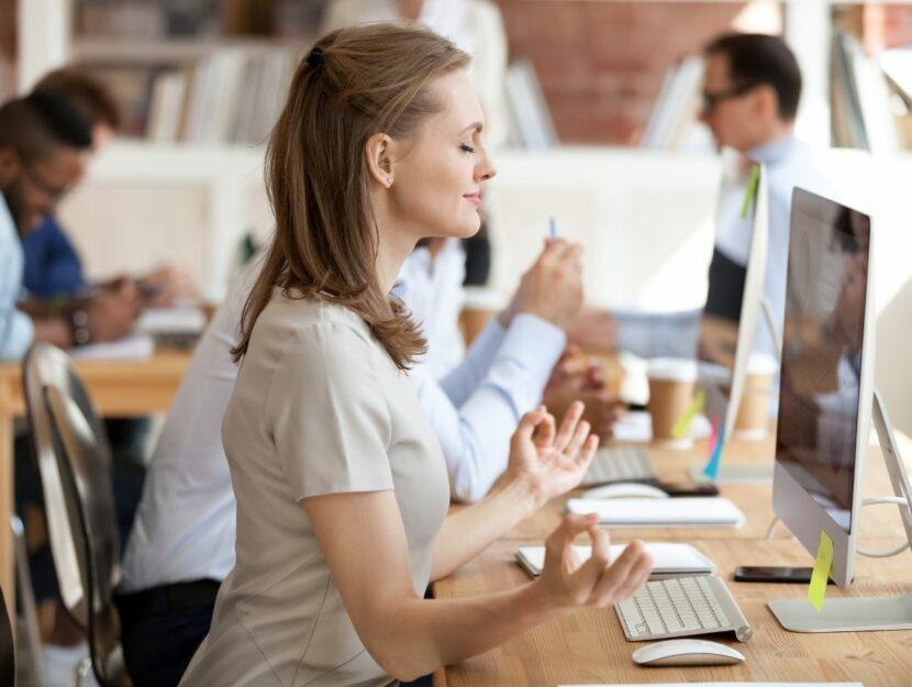 donna che medita alla scrivania, isolarsi dall'ufficio, cattive abitudini sul lavoro