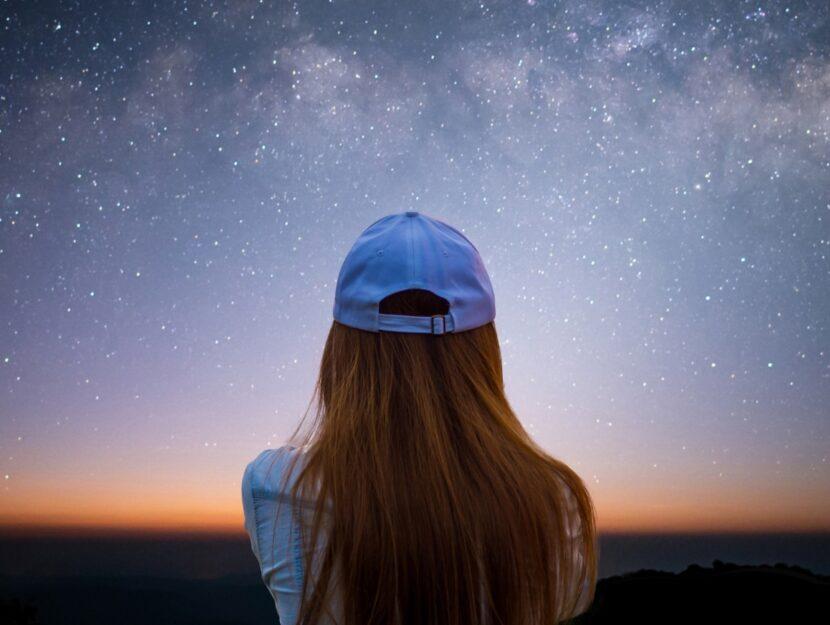ragazza con berretto che guarda il cielo