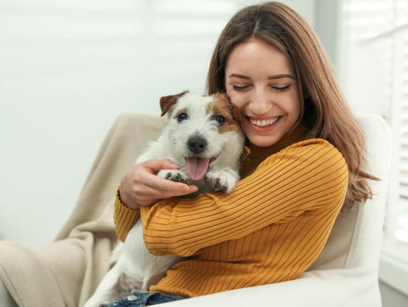 Donna felice con cane a casa