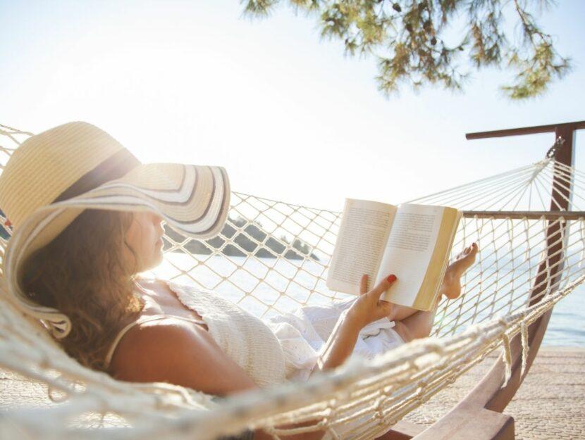 Donna legge un libro al mare