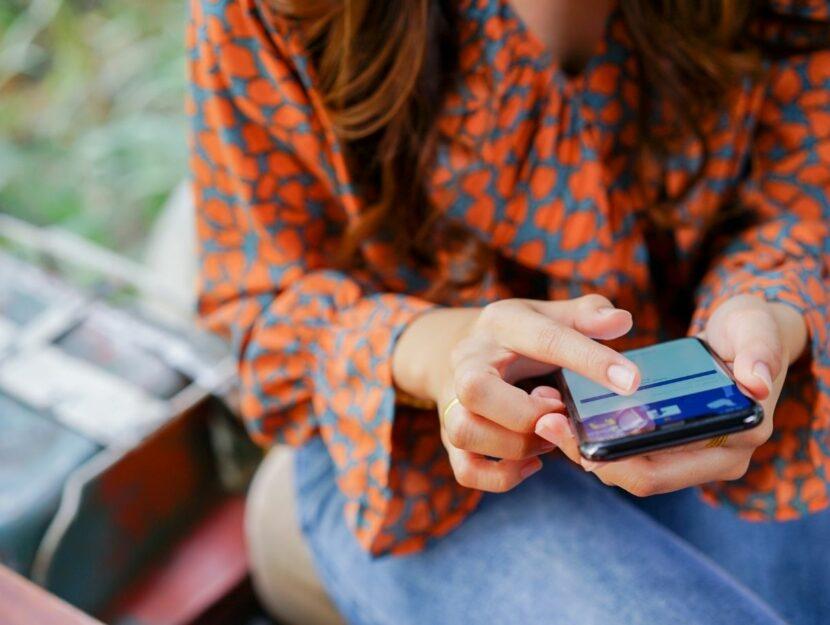 usare facebook nel 2021, donna che usa smartphone, camicetta elegante