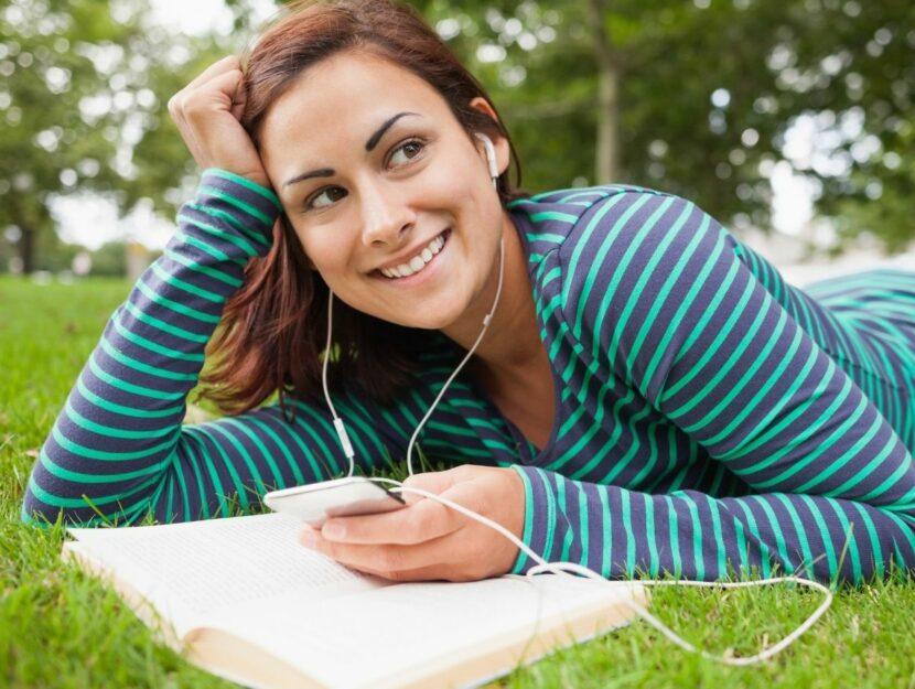 donna legge libro e ascolta musica