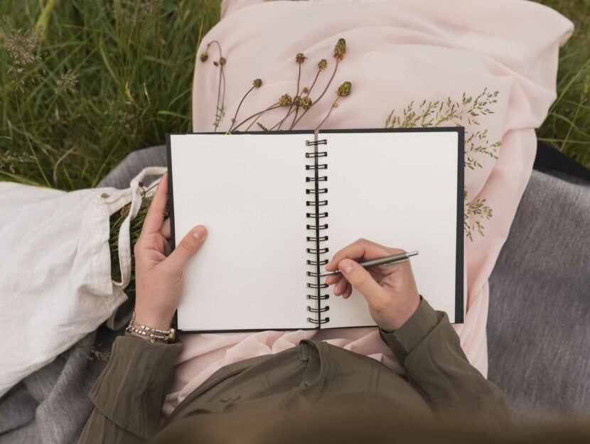 Donna scrive prato quaderno penna