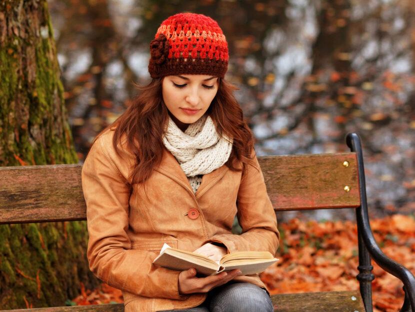 Ragazza capello libro panchina nel bosco autunno