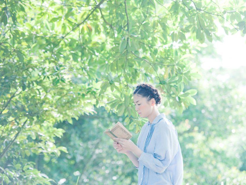 Ragazza giapponese legge libro alberi