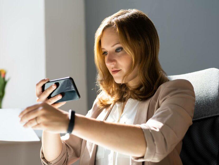 Donna che usa smartphone come scanner